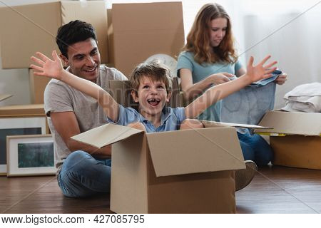 Happy Caucasian Father, Mother, Daughter And Son Sit On Wooden Floor Unpacking During Move New Home.