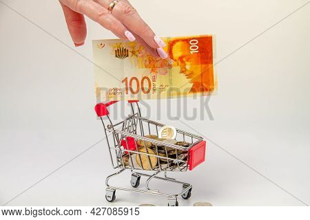 A Woman's Hand Holds A 100 Israeli Shekel Bill Over A Grocery Cart Filled With Israeli Coins On A Li