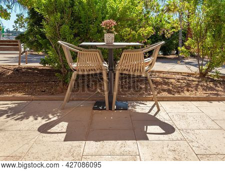 Table With A Decorative Potted Plant And Two Chairs Of A Restoration Establishment Without Customers
