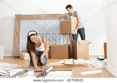 Couple moving in new home house. Young interracial couple in moving in mess. Asian woman, Caucasian man.