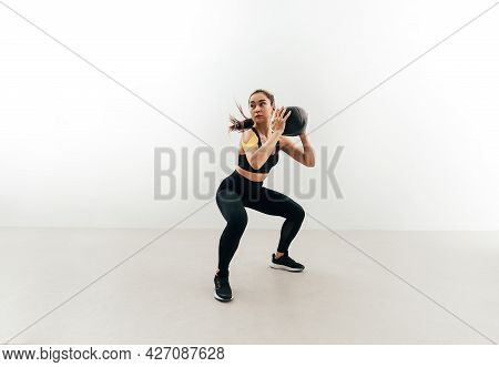 Muscular Woman Doing Sit-ups With Medicine Ball Indoors