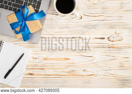 Top View Photo Of Beige Giftbox With Vivid Blue Ribbon Bow On Laptop Cup Of Coffee And Pen On Remind