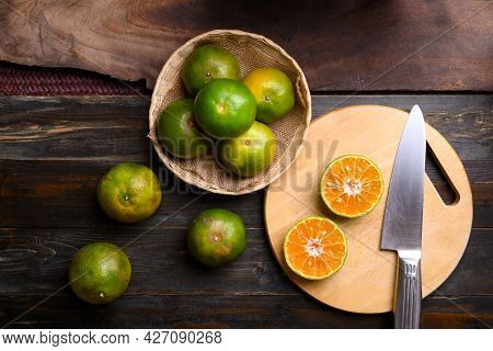 Green Tangerine Orange Fruit In A Bamboo Basket And Cutting On Wooden Board, Table Top View