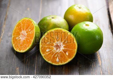 Green Tangerine Orange Fruit On Wooden Background