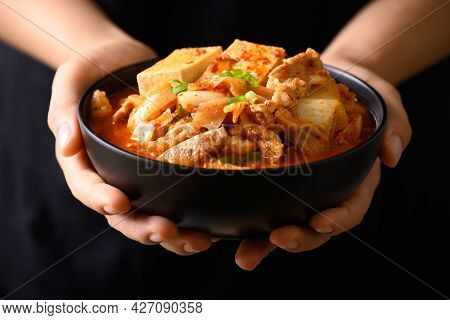 Korean Food, Kimchi Soup With Tofu And Pork In A Bowl Holding By Hand