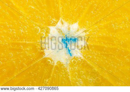 Orange Fruit In The Water Close-up Macro. Refreshing Grapefruit Drink, Cocktail. Slow Motion