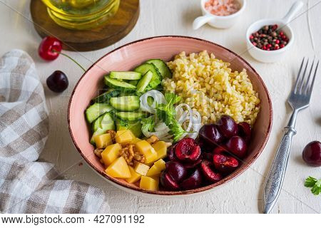 Healthy Salad Bowl With Bulgur, Cherry, Cheese, Cucumber And Walnuts On A Light Concrete Background.