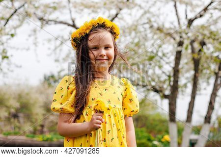 A Joyful, Smiling Girl With Hair Flying In The Wind With A Wreath Of Yellow Dandelions On Her Head,