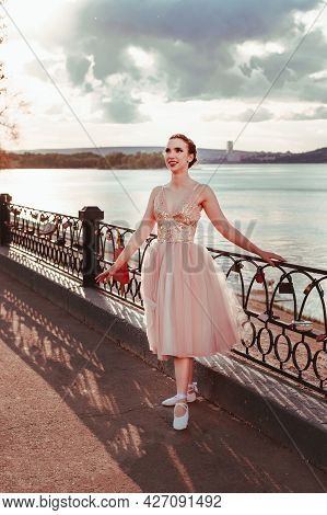 A Laughing, Smiling Ballerina In A Pink Silk Dress Poses Holding On To The Fence Of The Path Along T
