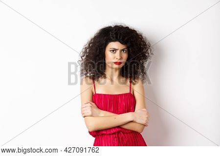 Sad And Offended Caucasian Woman In Red Dress Frowning, Cross Arms On Chest And Sulking, Feeling Mad