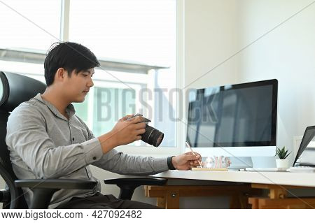 A Young Man Photographer Is Checking Previews On Camera While Sitting At His Workspace At Studio.