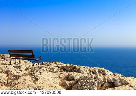 An Empty Bench At Cape Greco On The Island Of Cyprus. Relaxation Overlooking The Mediterranean Sea.