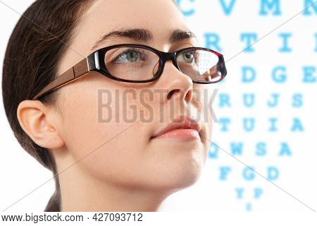 Healthy Vision. Close Up Face Of Young Beautiful Woman In Glasses Looking At A Diagram To Check Her
