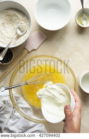Female Hands Cooking A Cake In Glass Bowl. Mixing Yougurt And Eggs In Glass Bowl, Step By Step Recip