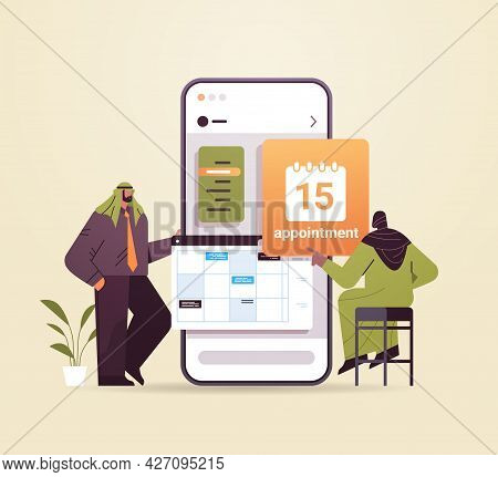 Arab Businesspeople Planning Day Scheduling Appointment In Calendar On Smartphone Screen Time Manage