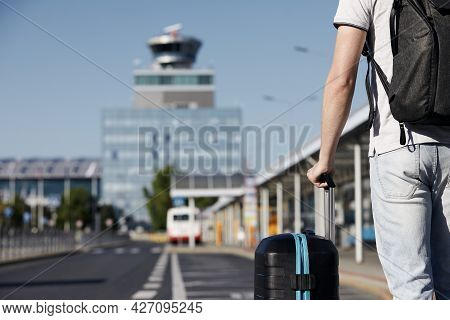 Passenger Walking From Bus Station To Airport Terminal. Selective Focus On Hand Holding Suitcace.