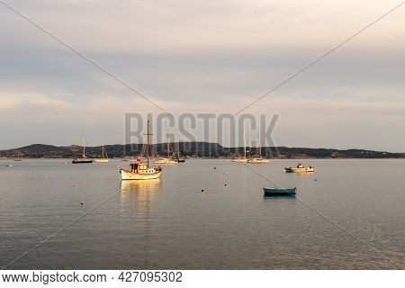 Fishing And Sailing Boats In Anchorage In Adamas Port On Milos Island, Greece During Golden Hour, Wi