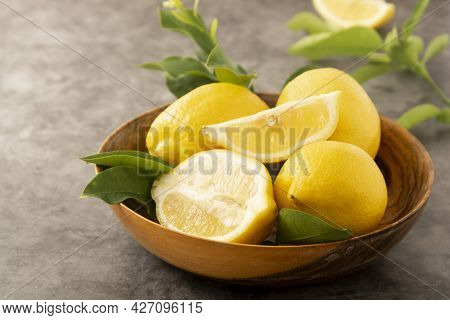 Lemons On Dark Background In Wooden Bowl. Citrus Fruits With Green Leaves.
