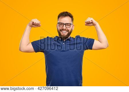Optimistic Bearded Man In Glasses Smiling And Looking At Camera While Showing Biceps Against Yellow