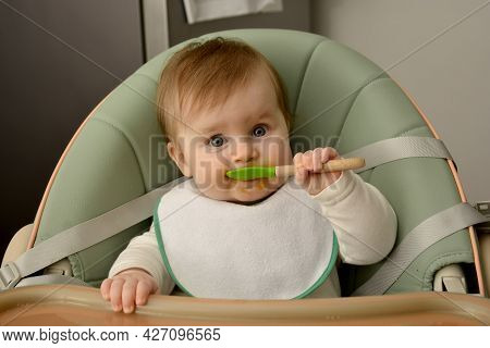 Baby Eating In Feeding Chair. 7 Month Cute Baby Girl Eating Her First Food.