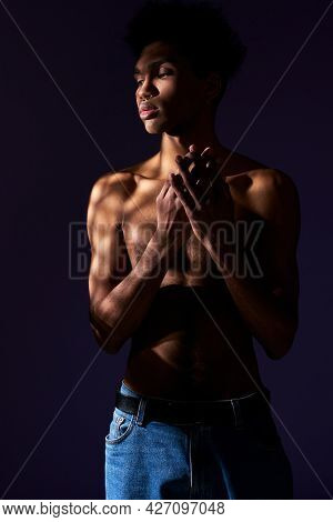Portrait Of Transgender Hispanic Model With Naked Torso. Trans Gender Young Man Standing In Shadow