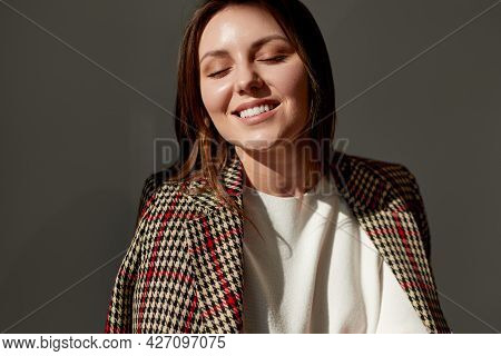 Delighted Young Female In Trendy Checkered Jacket Closing Eyes And Smiling While Enjoying Sunlight A
