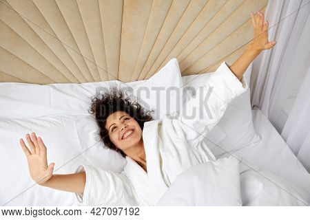 Smiling Woman Waking Up In Bed And Stretching Her Arms Up