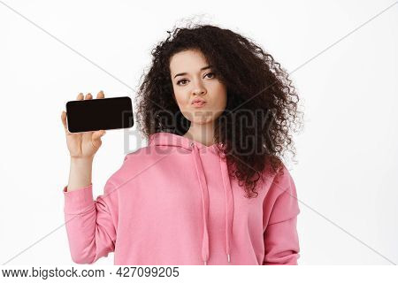 Disappointed Curly Brunette Girl Sulking, Showing Horizontal Smartphone Screen With Upset Face, Comp