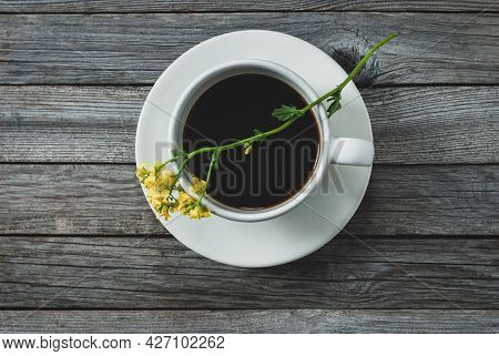 Cup Of Coffee And Yellow Flower On Wooden Table, Tabletop Shot