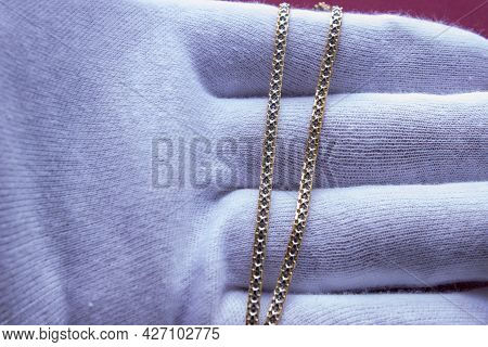 Gold Chain On The Hand In A White Glove Close-up. Jewelry Is Great For A Gift
