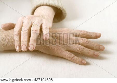 The Hands Of An Elderly Well-groomed Woman In A Casual Sweater. The Pensioner Has Crossed Her Beauti