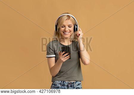 Favorite Leisure. Happy Millennial Woman In Wireless Headphones Listening Music Online On Smartphone