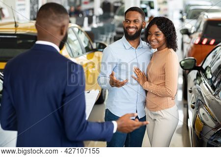 Young Black Couple Talking To Salesman In Dealership Office While Buying Car
