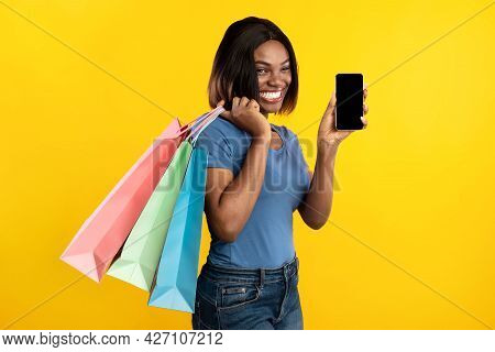 Black Lady Showing Phone Screen Holding Shopping Bags, Yellow Background