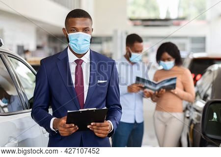 Portrait Of Handsome Black Car Salesman Wearing Mask At Workplace In Showroom