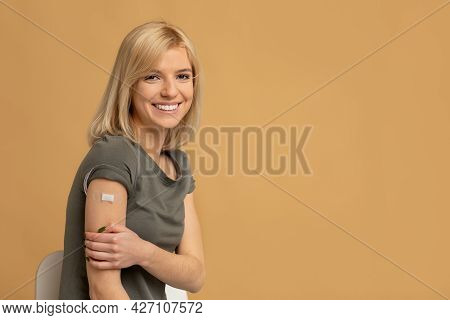 Coronavirus Vaccination Advertisement. Happy Vaccinated Lady Showing Arm With Plaster After Covid-19