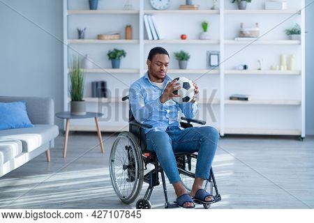 Depressed Handicapped Black Man In Wheelchair Looking At Soccer Ball With Sadness, Stressed About In