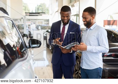 Black Male Customer In Car Dealership Center Looking At Brochure With Salesman