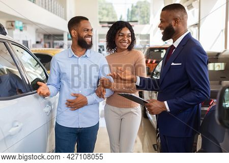 Happy Black Couple Talking To Salesman While Choosing Car In Dealership Center