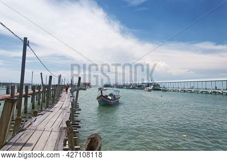 Penang, Malaysia.  August 21, 2017.  A Malaysian Man Walking On A Wooden Pier Near The Entrance Of T