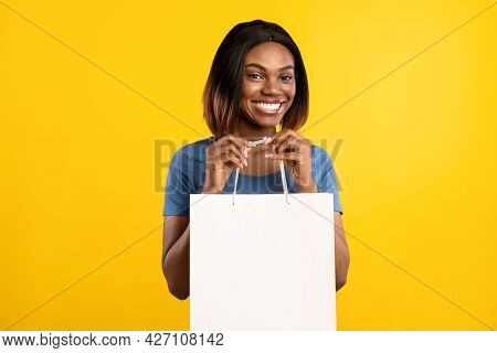 Toothy African American Lady Posing Holding Shopper Bag, Yellow Background