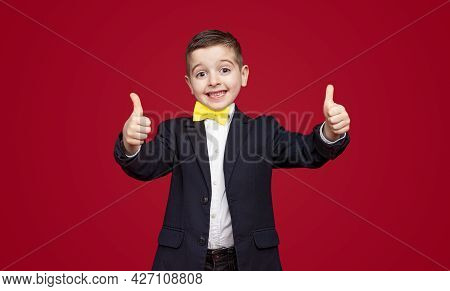Happy Smart Little Schoolboy In Formal Suit With Bow Tie Smiling And Gesturing Thumbs Up Against Red