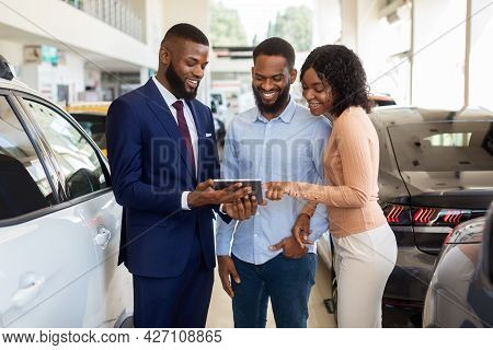 Dealership Center Manager Showing Vehicle Characteristics On Digital Tablet To Black Couple
