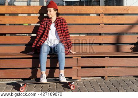 Carefree Young Hipster Girl Skateboarder Enjoy Sunlight Sitting On Wooden Bench With Feet On Longboa