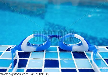 Blue Swimming Goggles On The Edge Of A Swimming Pool