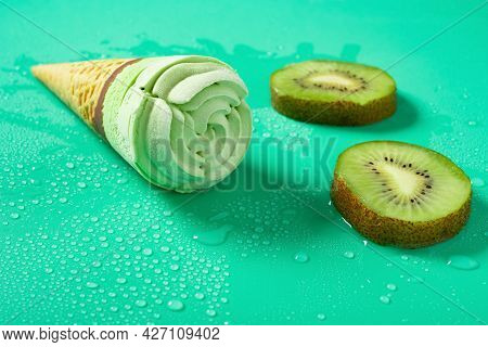 Angle View Fresh Kiwi Fruit Slices And A Kiwi Fruit Flavor Ice Cream Cone On Green Background