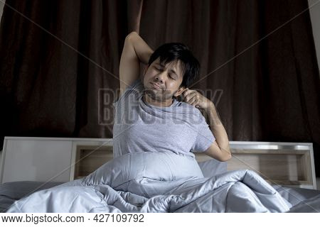 Asian Man Stretching On Bed After Wake Up In Morning