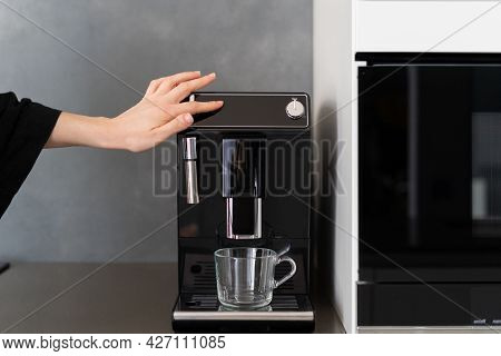 Cropped Shot Of Woman Pressing Button On Coffee Machine, Preparing It For Breakfast After Getting Up