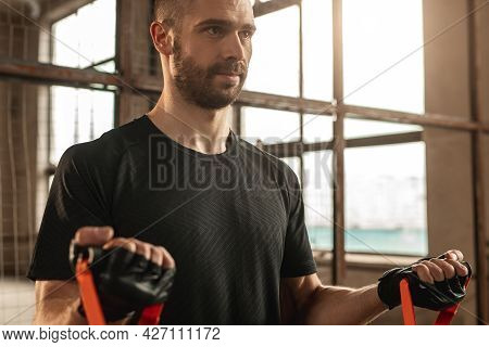 Powerful Determined Bearded Male In Sportswear Doing Exercises With Elastic Resistance Band During W