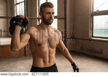 Strong Shirtless Bearded Male With Athletic Muscular Body Exercising With Heavy Kettlebell During In